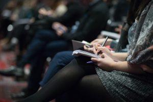 Vertreterinnen der Presse sitzen im Publikum mit Schreibblöcken auf dem Schoß und Stiften in der Hand (The Climate Reality Project)
