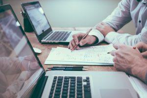 Zwei Personen besprechen an einem Schreibtisch zwischen zwei Laptops sitzend einen Text auf einem Blatt Papier (Scott Graham/Unsplash)