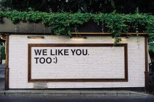 """Auf einer weißen Backsteinwand steht in großen schwarzen Buchstaben """"We like you. Too :)"""" (Adam Jang/Unsplash)"""